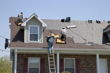 roofers replacing damaged shingles after storm